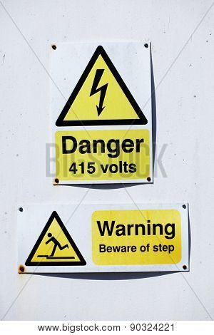High voltage danger warning sign for 415 volts of electricity with an additional warning to beware of a step below mounted on a white wall