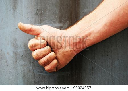 Male right hand showing thumbs up, sign of liking and approval, against a concrete gray wall, close-up
