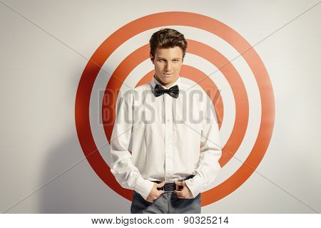 Elegant handsome man posing by a red shooting target. Spy man. Beauty, fashion.