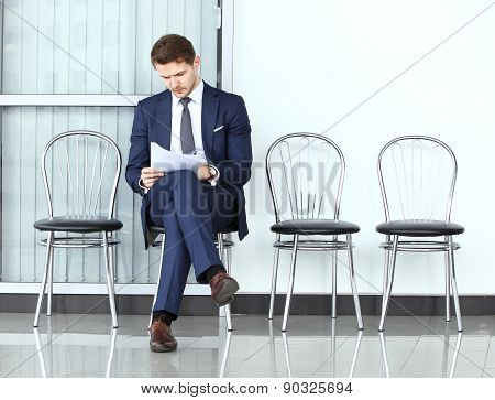 Ready For Interview. Thoughtful Man In Formalwear Holding Paper While Sitting At The Chair