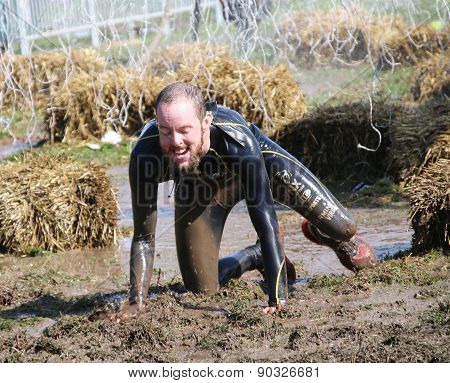 Man Covered With Mud Crawling Between Sheaf Of Hay