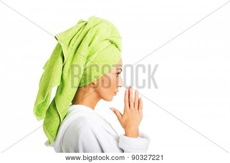 Side view woman in bathrobe clenching hands.