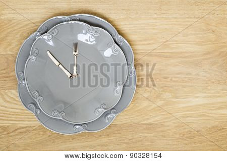 Grey Plate Clock On A Wooden Background