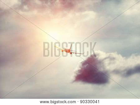 Travel background, silhouette of an airplane in the sky flies towards sun light, modern fast aircraft over cloudy and sunny skies, luxury airlines, transportation and airlift industry