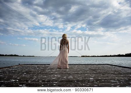 Back Of Blond Woman In Evening Gown Posing