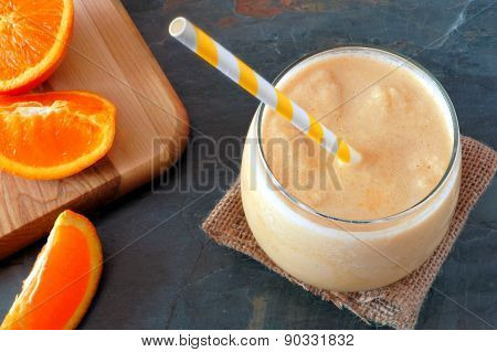 Orange smoothie with striped straw and fresh fruit slices