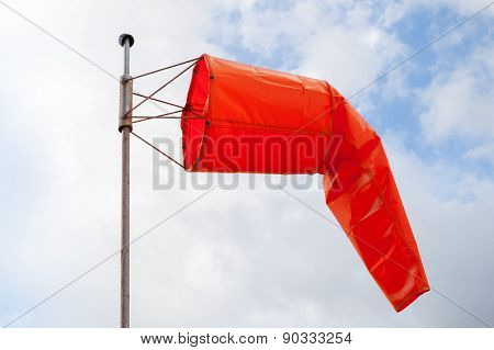 Windsock. Red Wind Indicator Over Cloudy Sky