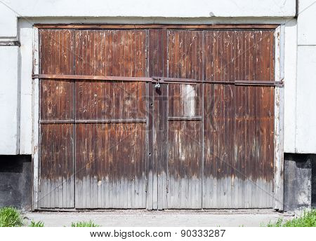Old Locked Wooden Gate In White Concrete Wall