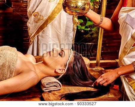 Young woman having oil Ayurveda spa treatment. Oil pouring from lamp.