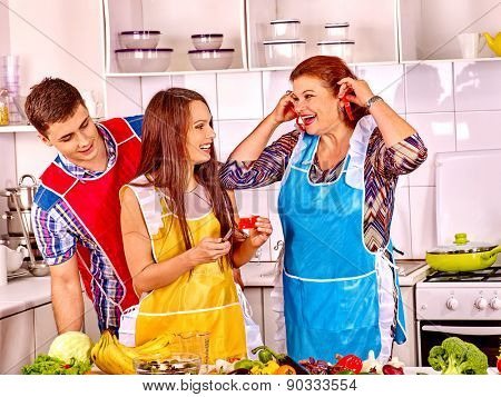 Mature woman with family preparing  dinner at home kitchen.