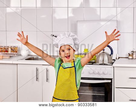Child wearing hat and apron cooking at kitchen. Hand up.