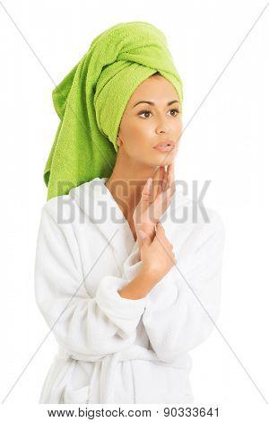 Portrait of a woman in bathrobe touching chin.