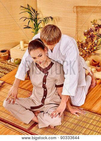 Male masseur doing massage young woman in bamboo spa. Sitting girl.