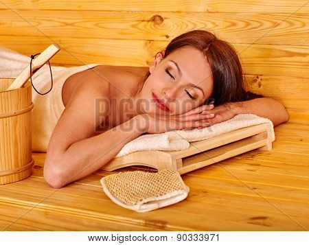 Young woman sleeping in sauna. Healthy lifestyle.