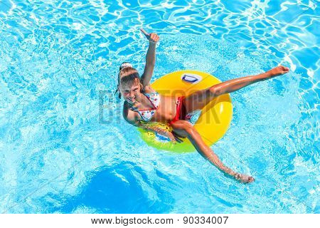 Little girl swimming on inflatable beach yellow ring. Thumb up.