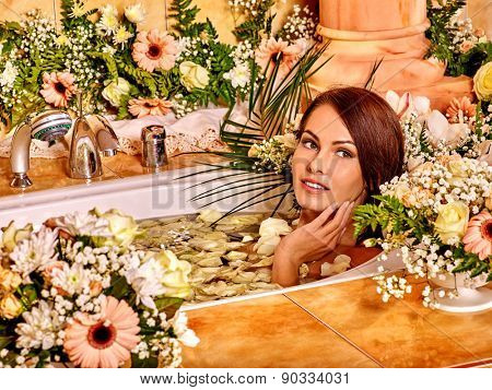 Woman lying in bath  applying moisturizer at bathroom.