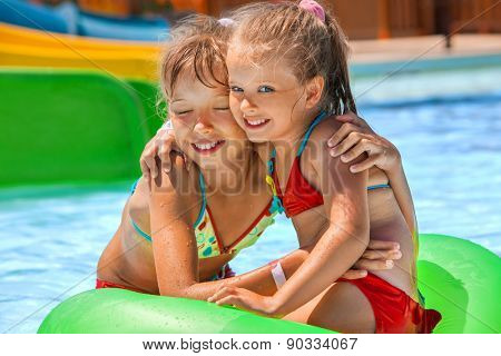 Two children sitting on green inflatable ring in swimming pool.