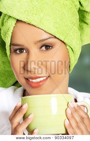 Beautiful spa woman in bathrobe with a cup.