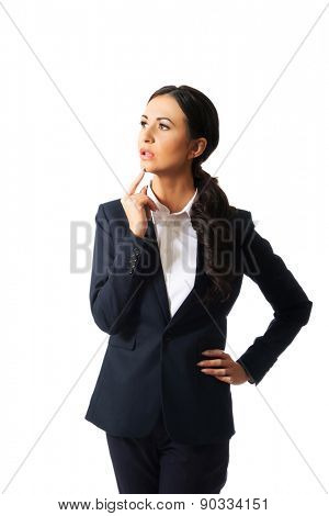 Thoughtful businesswoman with a finger under chin.