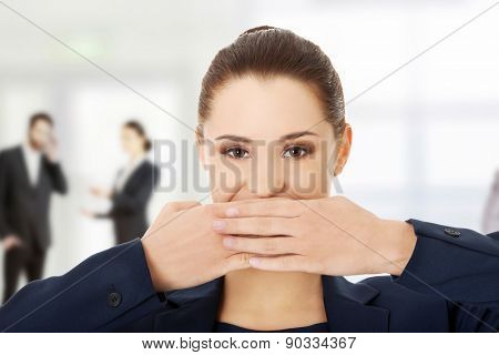 Young businesswoman covering with hand her mouth.