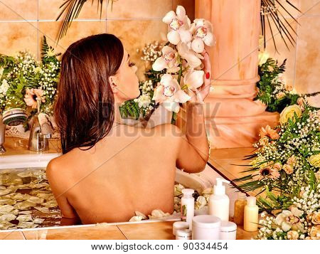 Woman applying moisturizer at bathroom. Bare back.