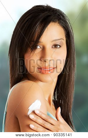 Beautiful spa woman with lotion on arm.