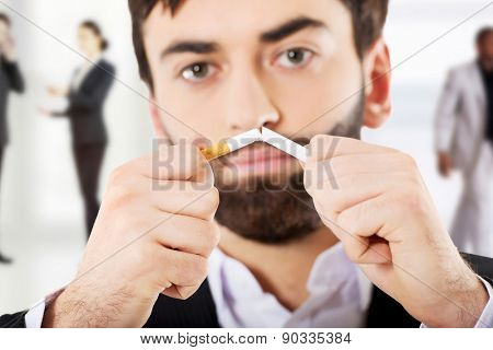 Handsome businessman breaking a cigarette.