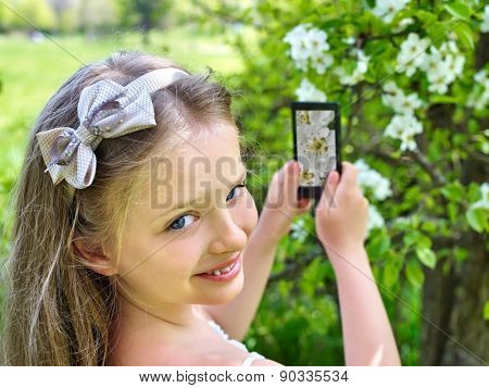 Girl snapshot blossoming cherry tree on  phone. Romantic style.