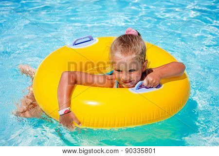 Child female on inflatable yellow ring in swimming pool.