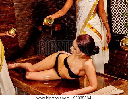Young woman having pouring oil spa treatment.