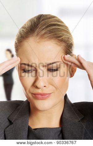 Beautiful businesswoman suffering from headache.