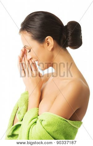 Spa woman wrapped in towel with closed eyes and clenched hands.
