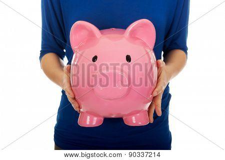 Young casual woman holding piggybank.