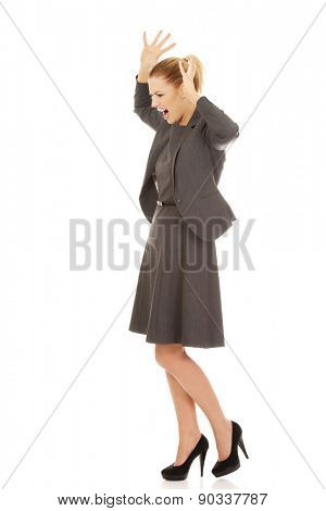 Angry caucasian businesswoman screaming loud.