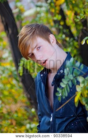 attractive, red-haired guy on nature. close-up portrait