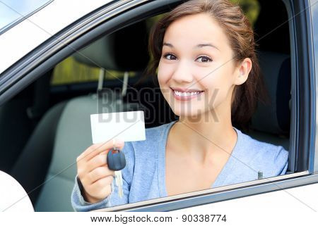 Happy girl in a car showing a key and an empty white card for your message