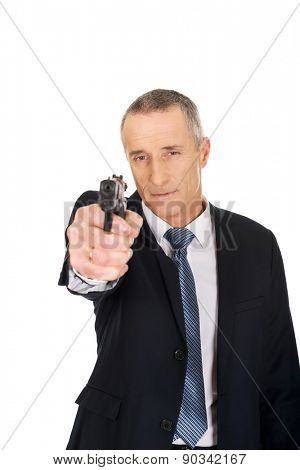 Serious mature mafia agent aiming by handgun.