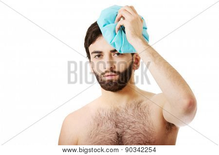 Shirtless man with headache and ice bag on his head.