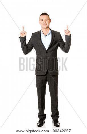 Handsome smiling businessman pointing upwards.