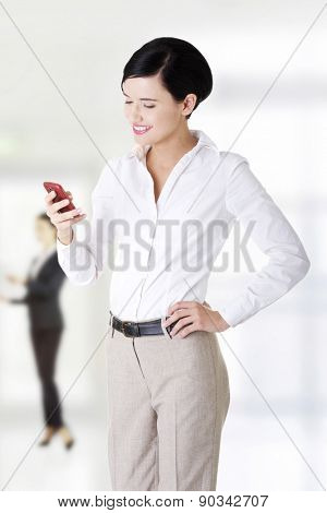 Happy business woman sending sms.