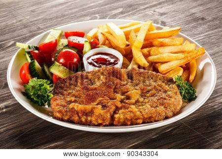 Fried pork chop, French fries and vegetable salad