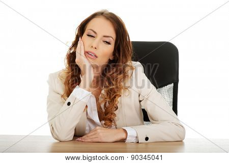 Beautiful exhautsed businesswoman at the desk.