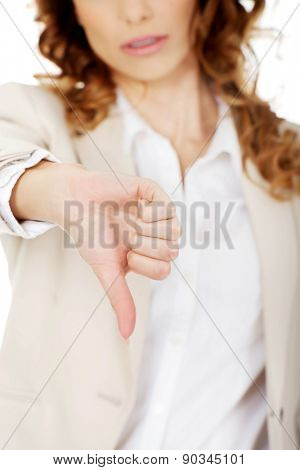 Unhappy businesswoman with thumbs down gesture.