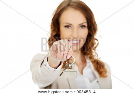Businesswoman real estate agent giving keys.