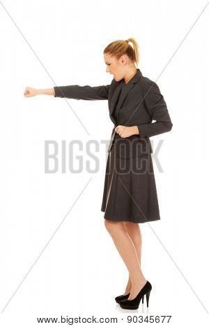 Angry businesswoman screaming and shaking her fist.