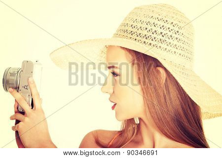 Portrait of a woman in hat taking photos.