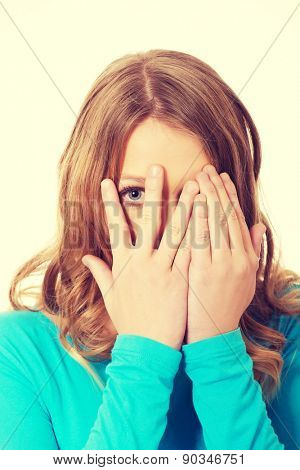Teenage woman covering her face with hands