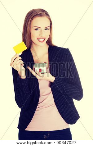 beautiful business woman holding a house and a personal yellow card. Isolated on white.
