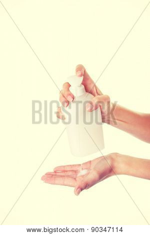 Young woman pouring body lotion on hand.