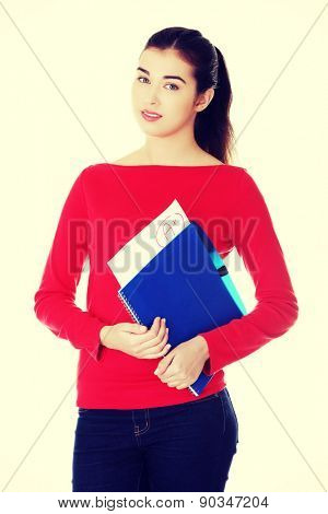 Pretty female student holding her notes.